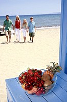 Bowl of fruit and parents with children on beach (thumbnail)
