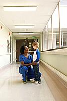 Nurse with patient in hospital corridor