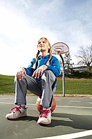 Girl sitting on basketball