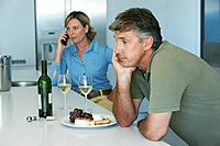 Husband looks upset while wive talks on cell phone
