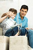 Father and son watering potted plant together, both smiling
