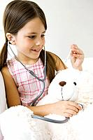 Little girl listening to teddy´s bear´s heart with stethoscope, looking at thermometer