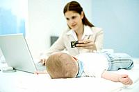 Young working mother making credit card purchase, baby lying on desk, focus on baby in foreground