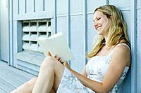 Young woman sitting outdoors, reading book, smiling