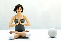 Woman sitting in lotus position beside ball, eyes closed