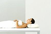 Woman lying on massage table, eyes closed