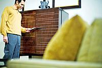 Man Looking at Price Tag Chest of Drawers