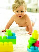 Baby crawling towards plastic blocks