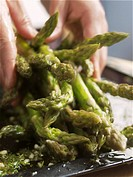 Hands putting cooked green asparagus on a plate