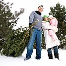 Family with Christmas tree outdoors