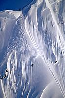 Aerial of extreme skiers skiing down steep mountain slope heli_skiing Chugach Mtns Southcentral Alaska