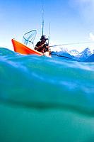 Male fishreman in kayak fishing for halibut in Resurrection Bay Seward Kenai Peninsula Alaska summer