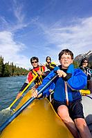 Young boy & family paddling on river raft Kenai River Kenai Peninsula Alaska Summer