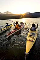Family sea kayaking in together into sunset on Bear Lake Kenai Peninsula Alaska Summer