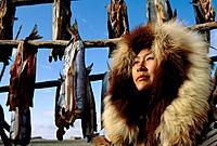 Alaskan Native Eskimo woman & fish drying rack Kotzebue/nAlaska Summer Fur parka