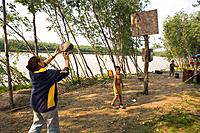 Native Yupik family take break from fishing playing basketball together @ fish camp Tuluksak WE Alaska