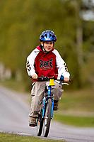 7 year old boy bicycle on a road, Vasterbotten, Sweden (June 2005)