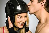 Young man kissing woman on helmet, studio shot