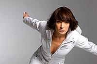 Young woman in white jumpsuit balancing, studio shot