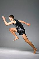 Young man sprinting off on one foot, studio shot