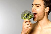 Close_up of young man eating broccoli