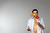 Mid adult man juggling peppers