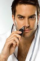 Mid adult man using nose hair trimmer