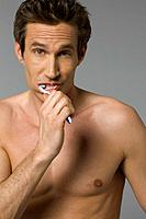 Close_up of mid adult man brushing teeth
