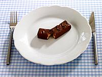 Close_up of a chocolate bar in a plate with a table knife and a fork