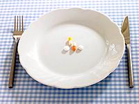 Close_up of pills and capsules in a plate with a fork and a table knife