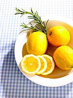High angle view of lemons with slices in a fruit bowl