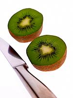Close_up of two halves of a kiwi fruit with a table knife