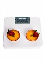 High angle view of fruit tarts on a weighing scale