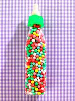 Close_up of a baby bottle filled with candies