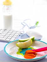 Close_up of baby food with apple slices in a plate with computer equipments