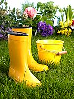 Close_up of a pair of rubber boots with a bucket