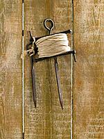 String with a hook hanging on a wooden plank