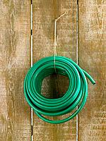 Rolled up garden hose hanging on a wooden plank