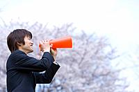 Young businessman holding a megaphone in the field of cherry blossoms, side view, Japan