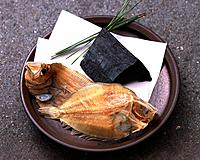 Closed Up Image of Two Dried Flatfish Next to a Piece of Coal on a Plate, High Angle View