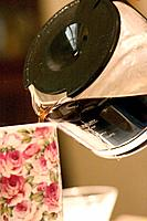 Pouring brewed coffee into a flowered mug