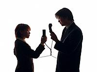 Bsinessman and businesswoman holding handsets and arguing, Side View, Silhouette
