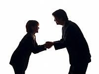 Bsinessman and businesswoman smiling and shaking hands, Side View, Silhouette