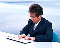 Image of a Businessman Typing Something on a Keyboard at the Beach, Side View