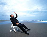 Image of a Businessman Sitting on a White Chair at the Beach, His Head Raised to the Sky, Side View