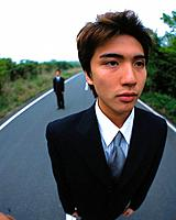 Closed Up Image of a Businessman Standing on a Road, With Another One in the Background, High Angle View, Differential Focus