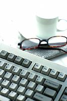 Keyboard, Coffee Cup, Newspaper and Glasses on the Desk, High Angle View