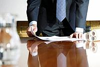 Businessman leaning on a boardroom table with blueprints.