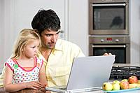 A father and daughter looking at a laptop