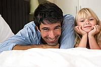 Father and daughter lying on a bed